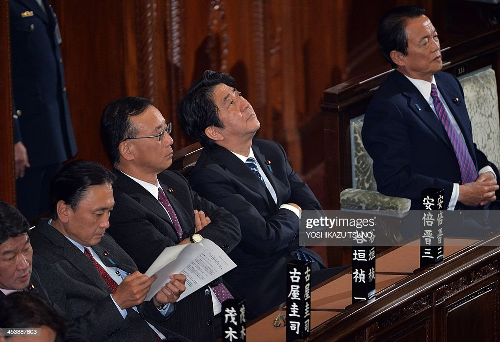 Japanese Prime Minister Shinzo Abe looks up after the Lower House unanimously passed a resolution criticizing China's expansion of its air defence...
