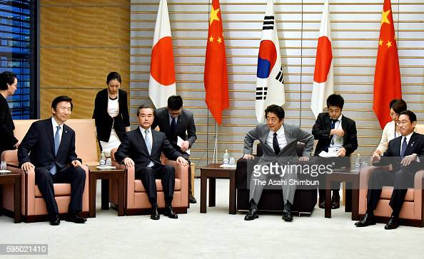 Japanese Prime Minister Shinzo Abe meets Japanese Foreign Minister Fumio Kishida his Chinese counterpart Wang Yi and South Korea's Yun Byungse at his...