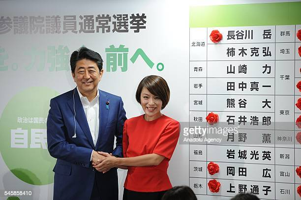 Japanese Prime Minister Shinzo Abe of the Liberal Democratic Party congratulates an elected candidate Imai Eriko as he places roses above names of...