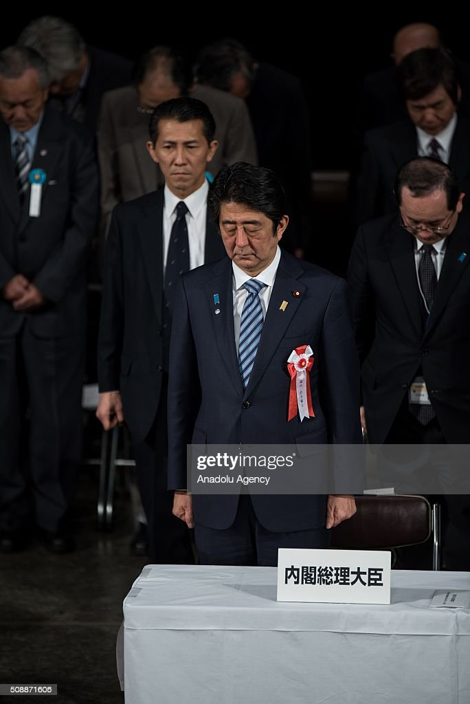 Japanese Prime Minister Shinzo Abe (C) offers a silent prayer for the deceased former Japanese residents of the Russia-controlled Southern Kurils, which Japan claims as the Northern Territories, during a government-backed annual convention calling for the return of the islands in Tokyo on February 7, 2015. Soviet troops took the islands in the final days of World War II, turfing out several hundred Japanese who lived there at the time. The issue has prevented the signing of a formal peace treaty between the two countries. {Nicolas Datiche/Anadoly Agency}