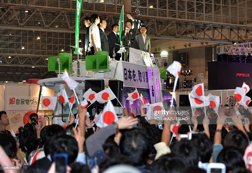 Japanese Prime Minister Shinzo Abe on a campaign car delivers a speech while his supporters wave Japan's national flags at an offline meeting sponsored by Japan's video sharing website 'Niconico Douga' (smiling video) in Chiba, suburban Tokyo on April 26, 2014. US President Barack Obama was all about business even at a special sushi dinner in Tokyo, which Abe wanted to use as a bonding opportunity. 'It was all about work,' Abe told his key ministers on April 25 night about his conversation with the US leader during their private dinner on April 23 at an exclusive Michelin-starred restaurant. AFP PHOTO / Yoshikazu TSUNO