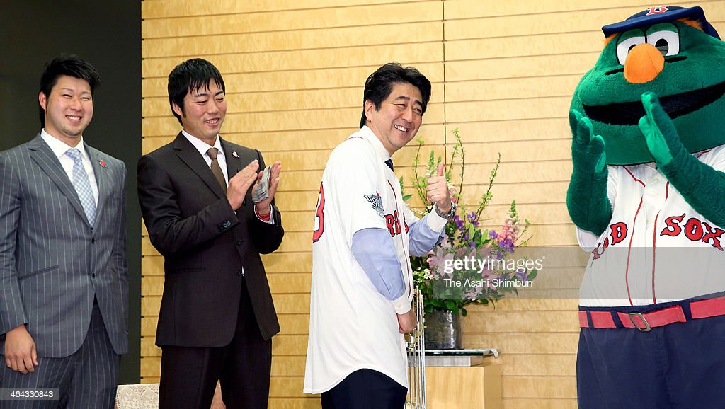 Japanese Prime Minister <a gi-track='captionPersonalityLinkClicked' href=/galleries/search?phrase=Shinzo+Abe&family=editorial&specificpeople=559017 ng-click='$event.stopPropagation()'>Shinzo Abe</a> (C) poses for photographs after being presented a Boston Red Sox shirt from pitchers <a gi-track='captionPersonalityLinkClicked' href=/galleries/search?phrase=Koji+Uehara&family=editorial&specificpeople=801278 ng-click='$event.stopPropagation()'>Koji Uehara</a> (2nd L) and <a gi-track='captionPersonalityLinkClicked' href=/galleries/search?phrase=Junichi+Tazawa&family=editorial&specificpeople=4624306 ng-click='$event.stopPropagation()'>Junichi Tazawa</a> (1st L) during their courtesy visit at Abe's official residence on January 21, 2014 in Tokyo, Japan.