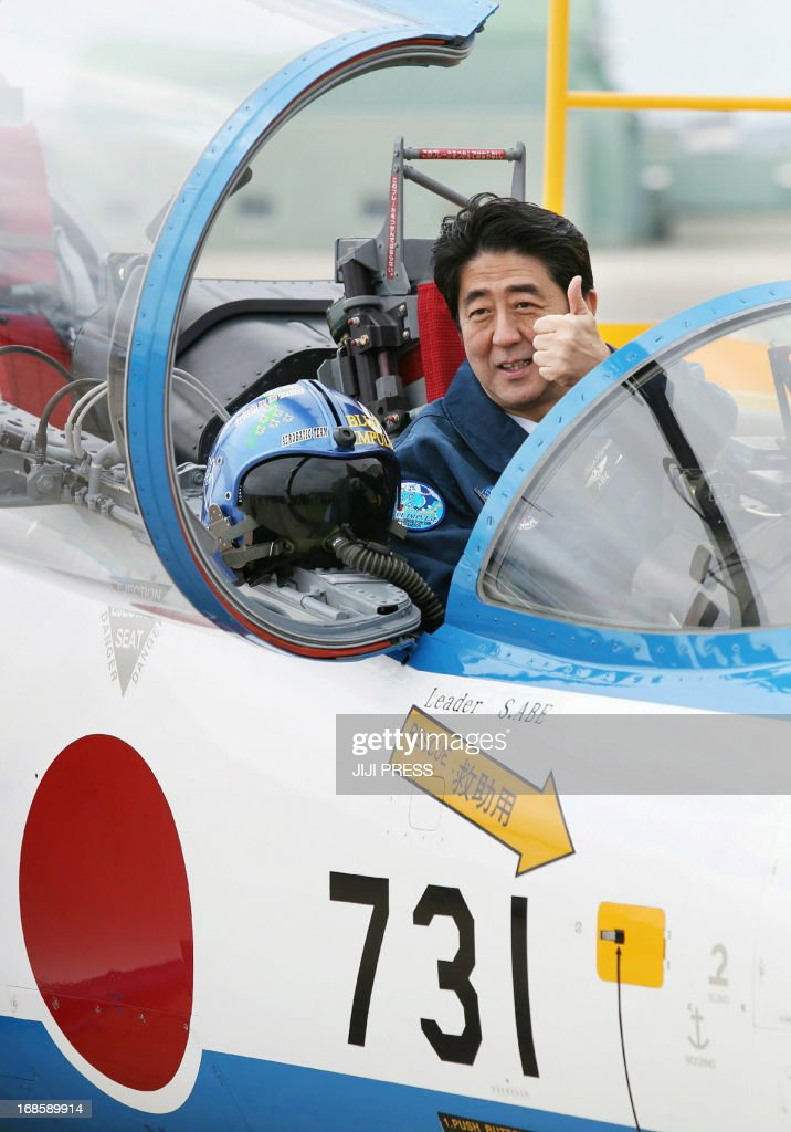 Japanese Prime Minister Shinzo Abe poses inside a T-4 training jet plane of the Air Self-Defense Force's Blue Impulse flight team at the ASDF base in Higashimatsushima, Miyagi prefecture on May 12, 2013 as part of his inspection tour of the March 11, 2011, earthquake and tsunami disaster areas.