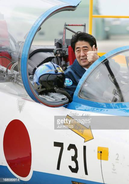 Japanese Prime Minister Shinzo Abe poses inside a T4 training jet plane of the Air SelfDefense Force's Blue Impulse flight team at the ASDF base in...