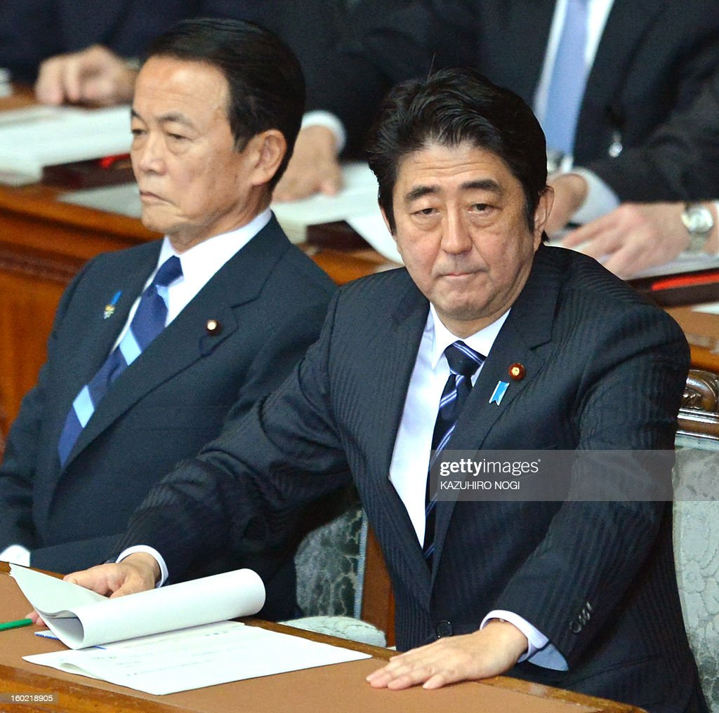 Japanese Prime Minister Shinzo Abe (R) prepares to deliver his first policy speech in the lower house plenary session as Finance Minister Taro Aso (L) looks on at the parliament in Tokyo on January 28, 2013. Abe pledged on January 28 he would not keep stimulus spending 'forever' in a policy speech ahead of a budget that will raise more in taxes than it does from borrowing.