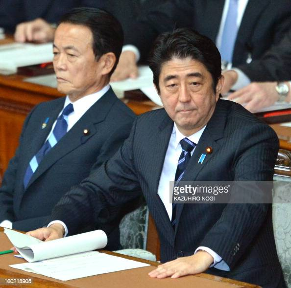 Japanese Prime Minister Shinzo Abe prepares to deliver his first policy speech in the lower house plenary session as Finance Minister Taro Aso looks...