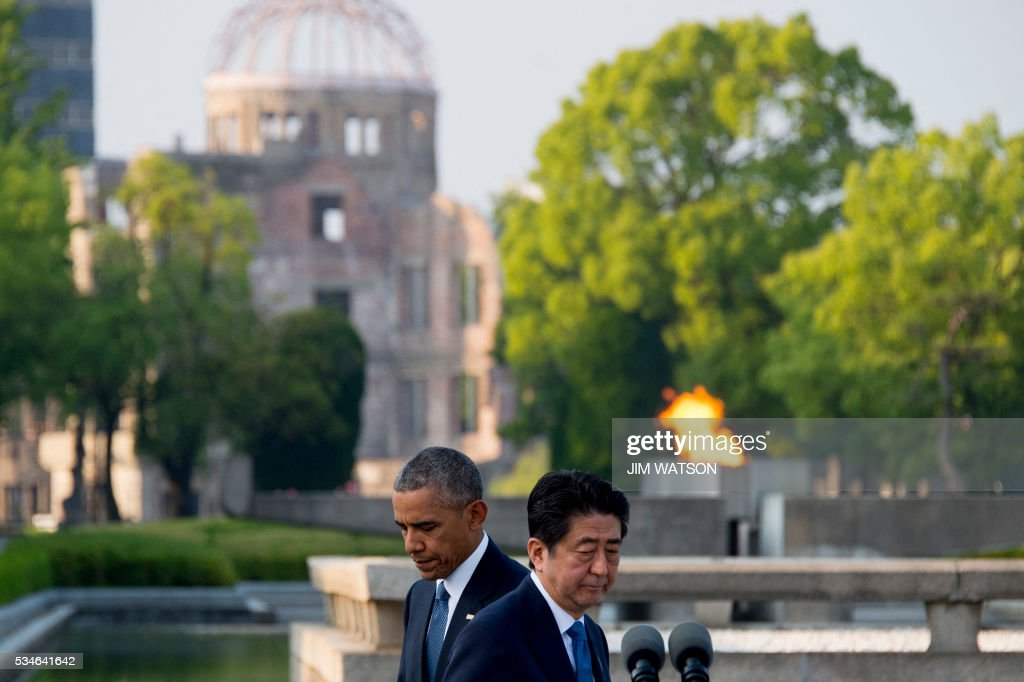 Japanese Prime Minister Shinzo Abe (front R) presents to speak after US President Barack Obama (L) made remarks after the two placed wreaths during a visit to the Hiroshima Peace Memorial Park in Hiroshima on May 27, 2016. Obama on May 27 paid moving tribute to victims of the world's first nuclear attack. WATSON
