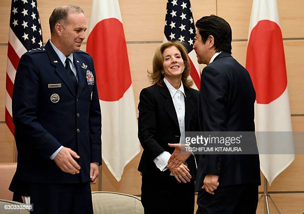 Japanese Prime Minister Shinzo Abe reaches his hand towards US Forces Japan commander Lieutenant General Jerry P Martinez while US Ambassador to...