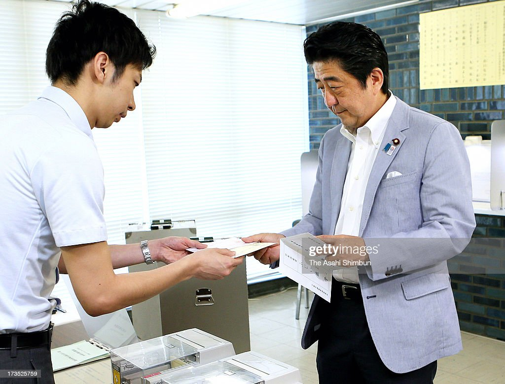 Japanese Prime Minister Shinzo Abe receives a ballot at an absentee vote center on July 16, 2013 in Tokyo, Japan. The upper house election will be held on July 21.