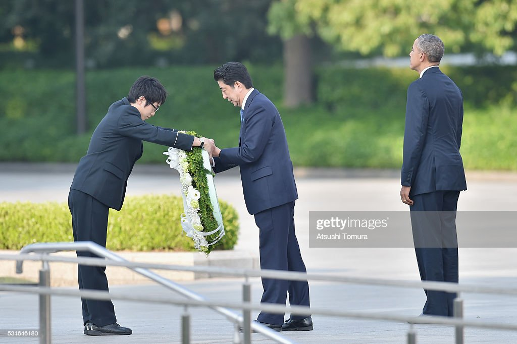 Japanese Prime Minister <a gi-track='captionPersonalityLinkClicked' href=/galleries/search?phrase=Shinzo+Abe&family=editorial&specificpeople=559017 ng-click='$event.stopPropagation()'>Shinzo Abe</a> (R) receives the flower to give as U.S. President Barack Obama stands next to him during U.S. President Obama's visit to the Hiroshima Peace Memorial Park on May 27, 2016 in Hiroshima, Japan. It is the first time U.S. President makes an official visit to Hiroshima, the site where the atomic bomb was dropped in the end of World War II on August 6, 1945.