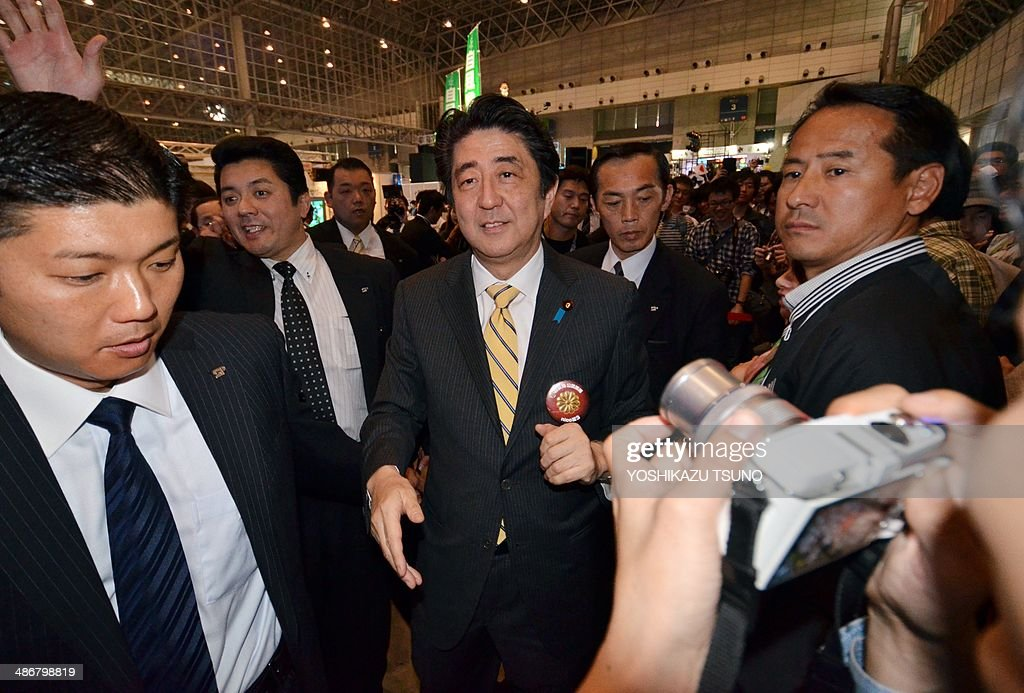 Japanese Prime Minister Shinzo Abe (C) shakes hands with his supporters at an offline meeting sponsored by Japan's video sharing website 'Niconico Douga' (smiling video) in Chiba, suburban Tokyo on April 26, 2014. US President Barack Obama was all about business even at a special sushi dinner in Tokyo, which Abe wanted to use as a bonding opportunity. 'It was all about work,' Abe told his key ministers on April 25 night about his conversation with the US leader during their private dinner on April 23 at an exclusive Michelin-starred restaurant. AFP PHOTO / Yoshikazu TSUNO