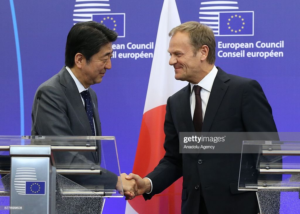 Japanese Prime Minister Shinzo Abe (L) shakes hands with the President of the European Council Donald Tusk (R) following a joint press conference after the EU - Japan leaders' meeting at the EU headquarters in Brussels on May 3, 2016.