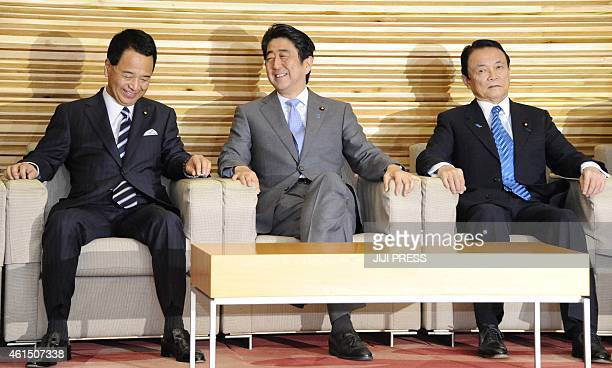 Japanese Prime Minister Shinzo Abe shares a light moment with Economic Revitalization Minister Akira Amari and Finance Minister Taro Aso during a...