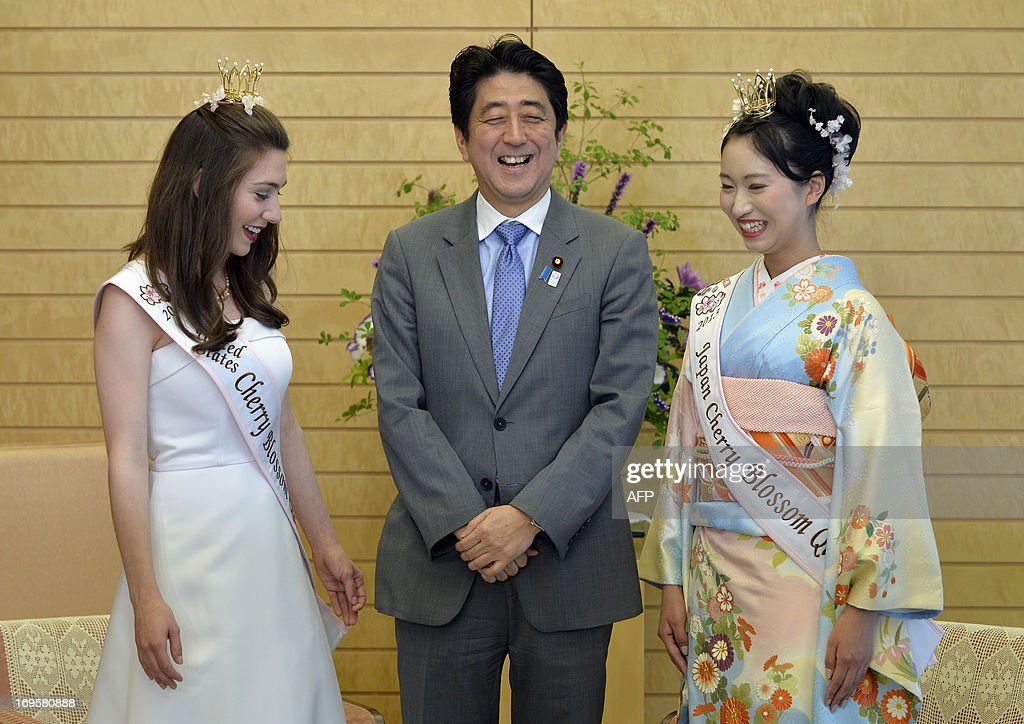 Japanese Prime Minister Shinzo Abe (C) shares a light moment with US Cherry Blossom Queen Mary Anne Morgan (L) from Oklahoma and Japan's Cherry Blossom Queen Chiori Kobayashi (R) during a courtesy call at the prime minister's official residence in Tokyo on May 28, 2013. Morgan won the title in April and is serving as a goodwill ambassador to Japan.