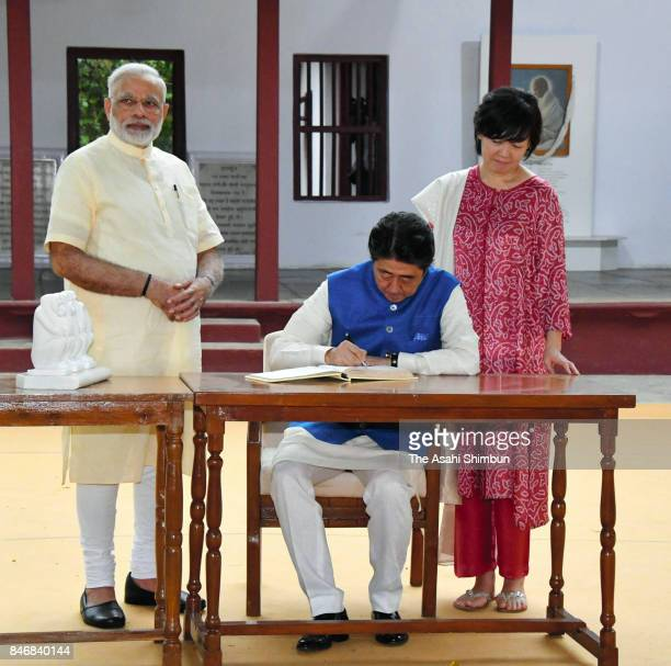 Japanese Prime Minister Shinzo Abe signs vistors' book while his wife Akie and Indian Prime Minister Narendra Modi watch at Sabarmati Ashram on...