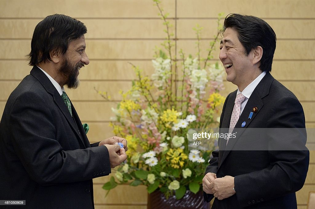 Japanese Prime Minister Shinzo Abe (R) smiles after he gave Indian Nobel Peace Price laureate and Chairman of the Intergovernmental Panel on Climate Change (IPCC) <a gi-track='captionPersonalityLinkClicked' href=/galleries/search?phrase=Rajendra+Pachauri&family=editorial&specificpeople=4128691 ng-click='$event.stopPropagation()'>Rajendra Pachauri</a> (L) a Japanese Environment Ministry's 'Fun to Share' badge at the premier's official residence in Tokyo on March 28, 2014. International scientists are holding a week-long meeting in Japan that is set to deliver dark predictions on the impact of climate change, warning of severe floods and droughts that could spark conflict and wreck economies.