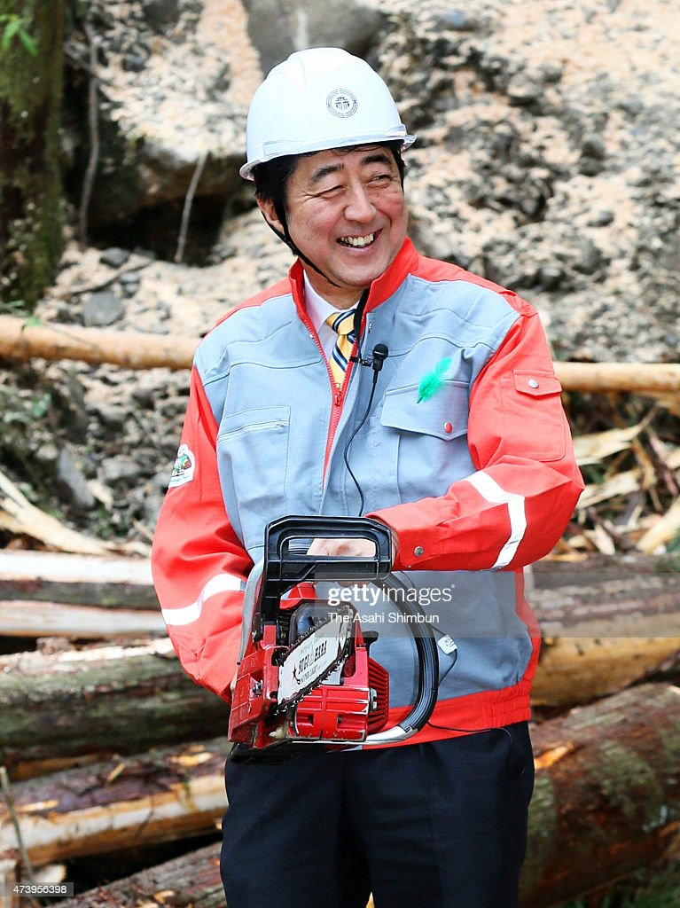 Japanese Prime Minister Shinzo Abe smiles as he holds a chain saw as he inspects the forest industry on May 17 2015 in Tanabe Wakayama Japan Abe is...