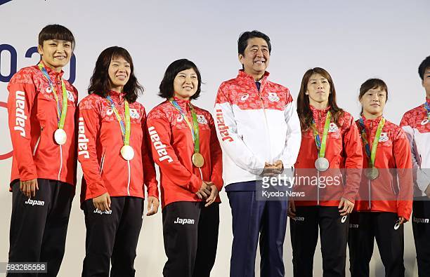 Japanese Prime Minister Shinzo Abe smiles as he is flanked by women's wrestling medalists from his country Kaori Icho Risako Kawai Sara Dosho Saori...
