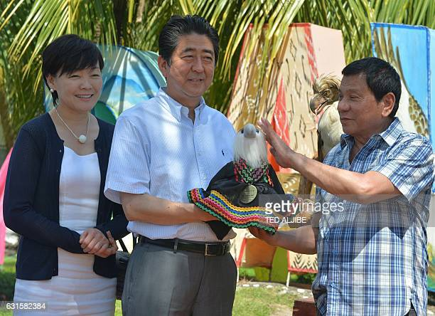 Japanese Prime Minister Shinzo Abe smiles as Philippine President Rodrigo Duterte touches the Philippine eagle stuffed toy as he hands over it to Abe...