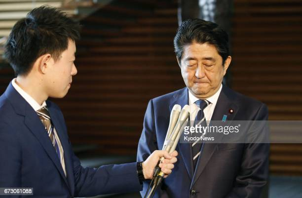 Japanese Prime Minister Shinzo Abe speaks at his office in Tokyo on April 26 about the resignation of disaster reconstruction minister Masahiro...