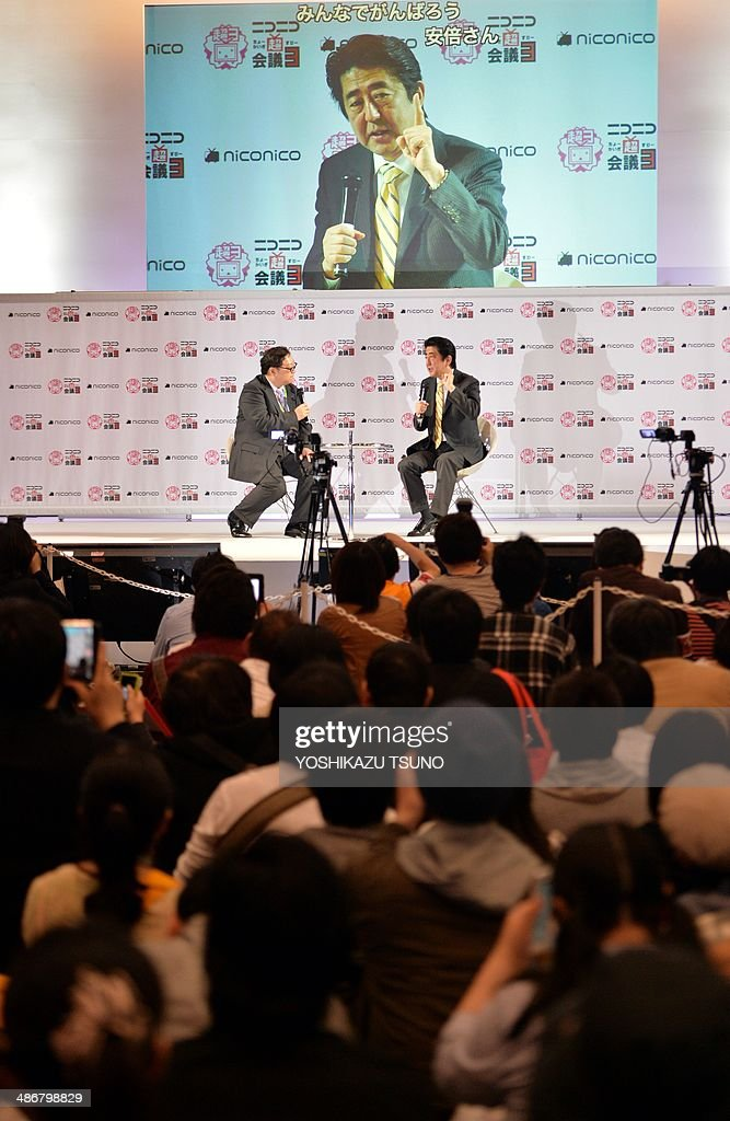 Japanese Prime Minister Shinzo Abe (R) speaks before his supporters at an offline meeting sponsored by Japan's video sharing website 'Niconico Douga' (smiling video) in Chiba, suburban Tokyo on April 26, 2014. US President Barack Obama was all about business even at a special sushi dinner in Tokyo, which Abe wanted to use as a bonding opportunity. 'It was all about work,' Abe told his key ministers on April 25 night about his conversation with the US leader during their private dinner on April 23 at an exclusive Michelin-starred restaurant. AFP PHOTO / Yoshikazu TSUNO