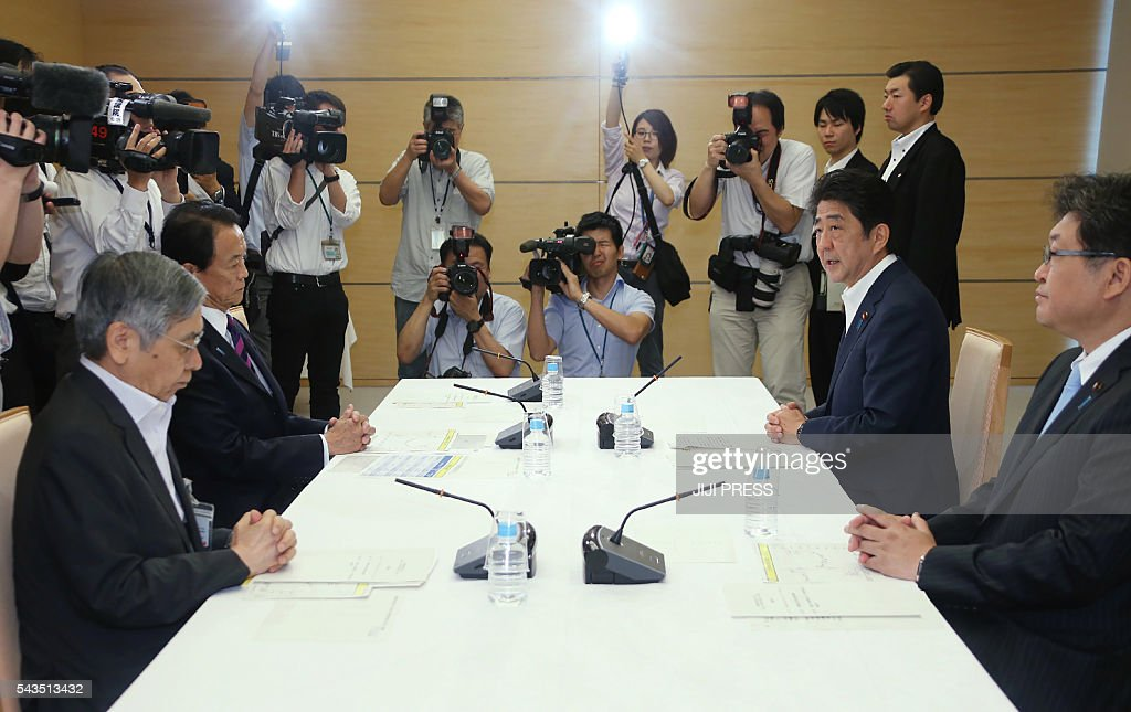 Japanese Prime Minister Shinzo Abe (2nd R) speaks during an emergency meeting as Finance Minister Taro Aso (2nd L) and Bank of Japan Governor Haruhiko Kuroda (L) attend to discuss the impact of Britain's vote to exit the European Union, at Abe's official residence in Tokyo on June 29, 2016. The government, central bank and business leaders have been meeting several times since the British decision to assess how Japan can best limit its impact on the world's number three economy. / AFP / JIJI PRESS / JIJI PRESS / Japan OUT