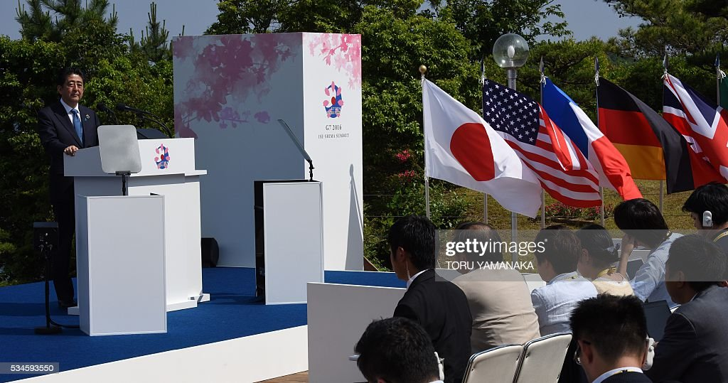 Japanese Prime Minister Shinzo Abe (L) speaks to journalists at a press conference at the end of the two-day Group of Seven (G7) Summit meeting at Shima on May 27, 2016. Pumping up the world economy is an 'urgent priority' G7 leaders said on May 27, but left the door open for a go-your-own-way approach in a sign of lingering divisions over how to boost growth. / AFP / TORU