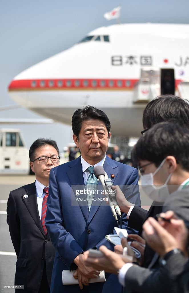 Japanese Prime Minister Shinzo Abe (C) speaks to journalists prior to his departure for major European countries at Tokyo's Haneda airport on May 1, 2016. Abe will visit Italy, France, Belgium, Germany, Britain, and Russia during his week-long diplomatic trip. / AFP / KAZUHIRO