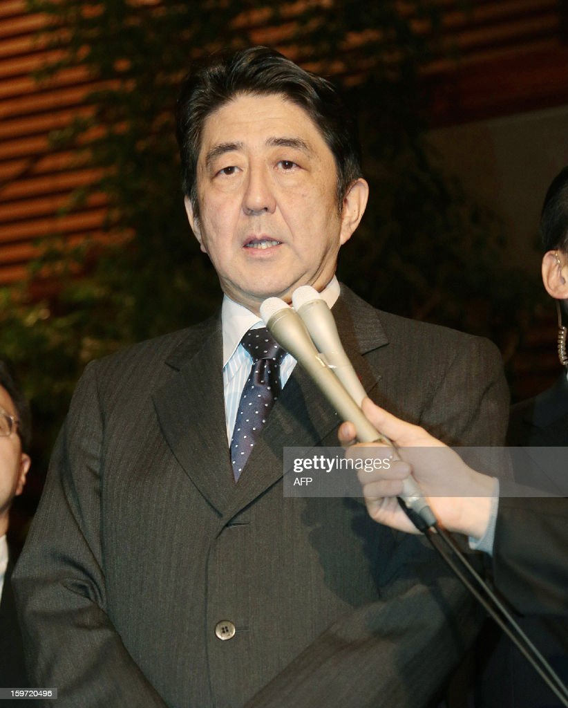 Japanese Prime Minister Shinzo Abe (C) speaks to reporters outside his office in Tokyo after a telephone conversation with his Algerian counterpart Abdelmalek Sellal on January 20, 2013. Prime Minister Shinzo Abe on Saturday ordered his government to do everything possible to ensure the safety of 10 Japanese unaccounted for in the 'despicable' hostage-taking in Algeria. Energy giant BP said Saturday that four of its employees remained missing following the attack on the In Amenas gas plant in Algeria, and CEO Bob Dudley said he feared for their lives. AFP PHOTO / JIJI PRES JAPAN OUT