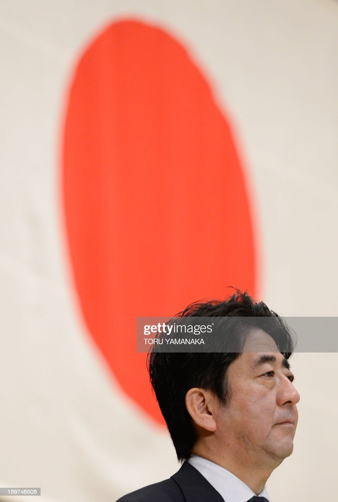 Japanese Prime Minister Shinzo Abe (C) speaks to troops as he attends flag return ceremony for the the United Nations assigned Japanese platoon at the Defence Ministry in Tokyo on January 20, 2013. All Japanese soldiers recently returned from United Nations peacekeeping operations assignment in the Golan Heights. AFP PHOTO/Toru YAMANAKA