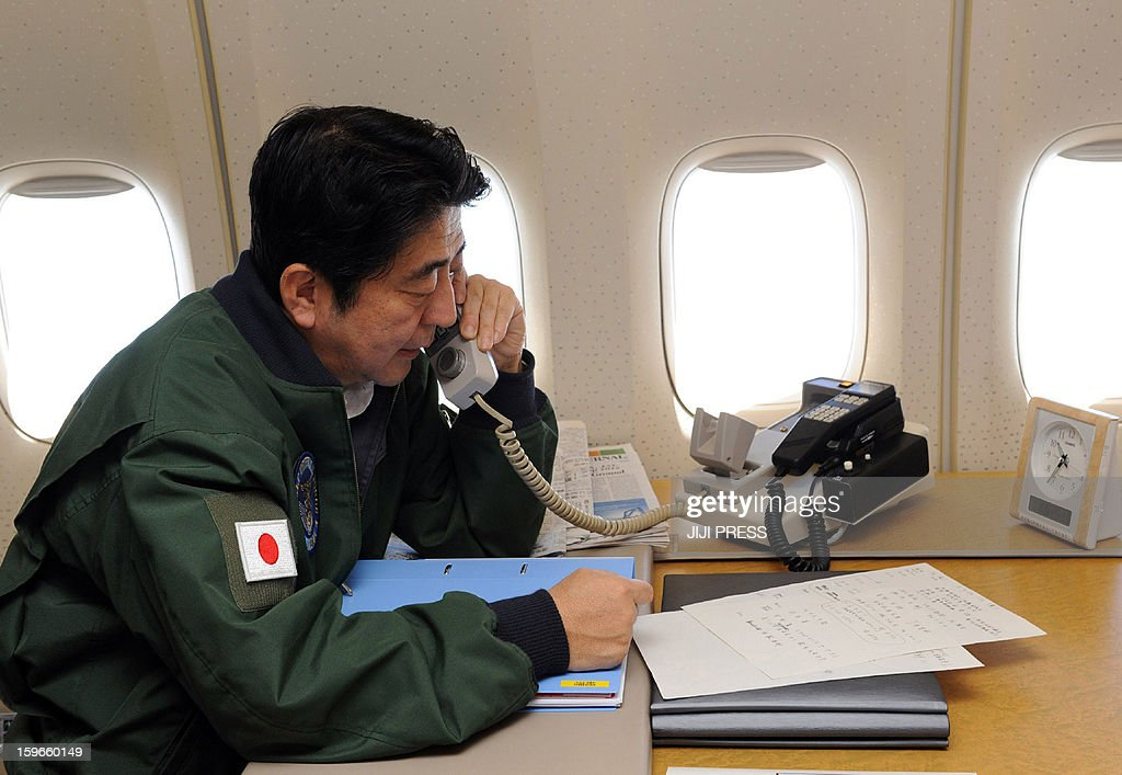 Japanese Prime Minister Shinzo Abe talks on a phone at his office while in flight on a government plane heading to Jakarta from Bangkok on January 18, 2013. Abe is to cut short his visit to Indonesia, to fly home and deal with the hostage crisis in Algeria on January 19 in which numerous Japanese are caught up. Abe is on the final leg of his first foreign trip since returning to office late last year. JAPAN