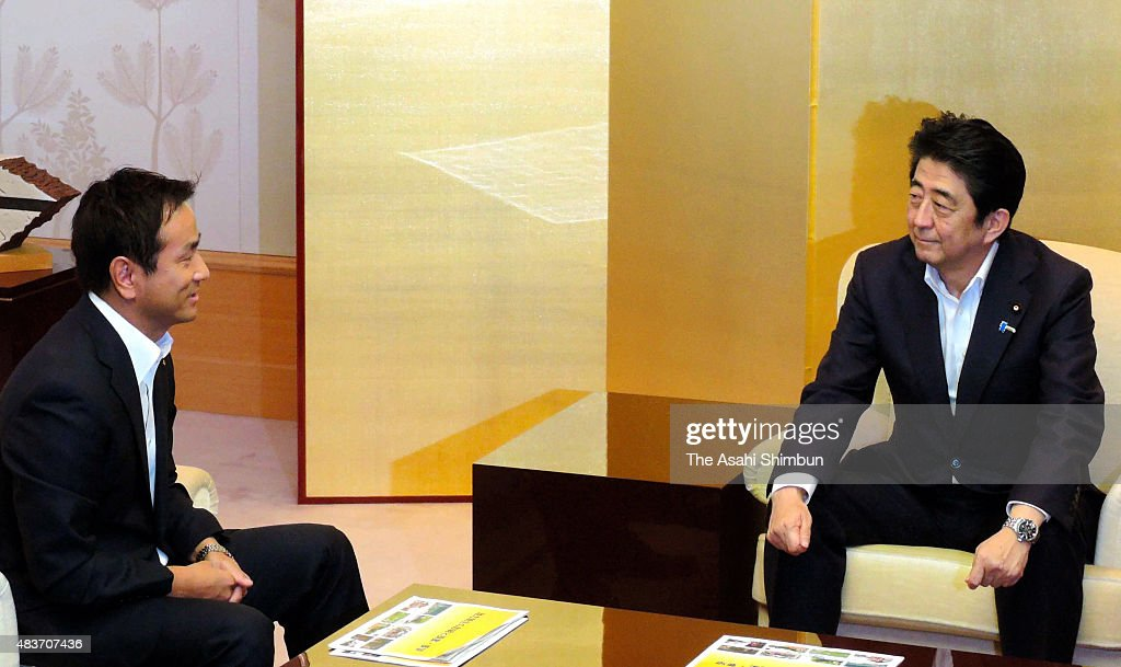 Japanese Prime Minister Shinzo Abe talks with Yamaguchi Prefecture Governor Tsugumasa Muraoka during their meeting on August 12 2015 in Yamaguchi...