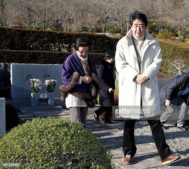 Japanese Prime Minister Shinzo Abe visits the grave of his grandfather Nobusuke Kishi with his mother Yoko at Fuji Cemetery on January 11 2015 in...