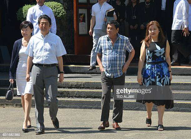 Japanese Prime Minister Shinzo Abe walks with Philippine President Rodrigo Duterte and their wives Akie Abe and Honeylet Avancena on their way to...