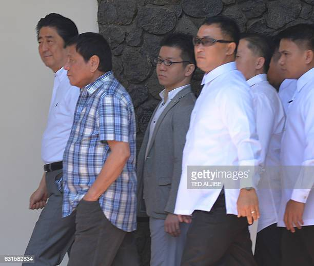 Japanese Prime Minister Shinzo Abe walks with Philippine President Rodrigo Duterte on their way to their oneonone meeting in Davao City in southern...