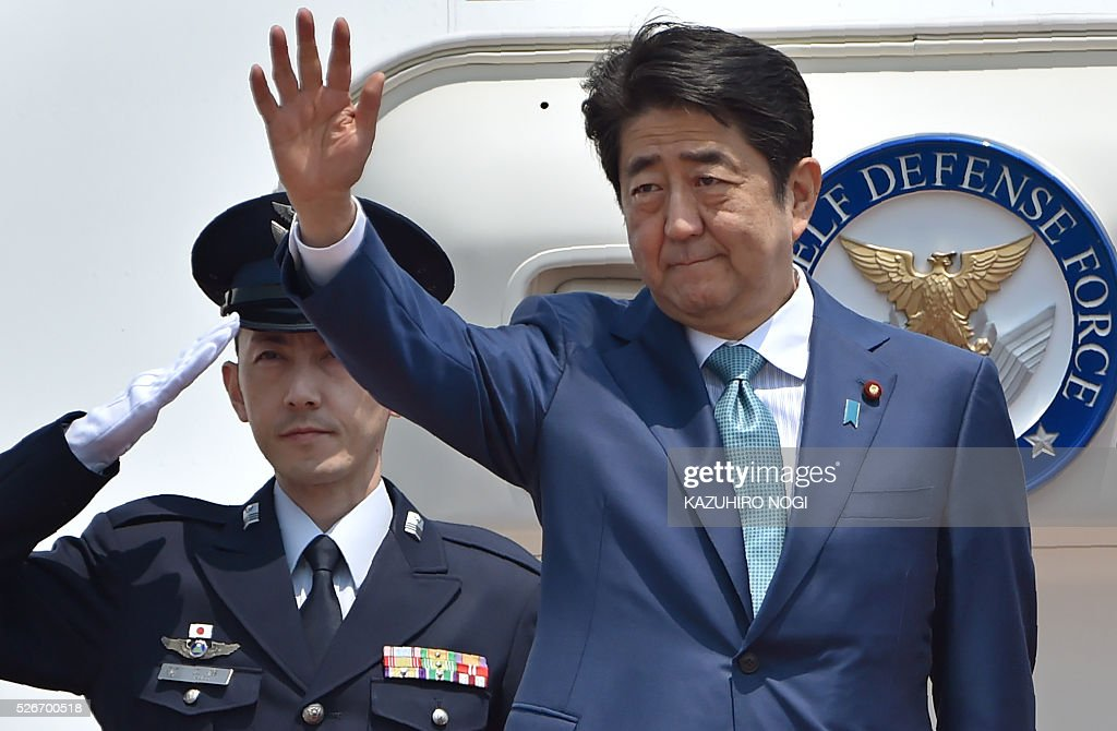 Japanese Prime Minister Shinzo Abe (R) waves as he departs for major European countries at Tokyo's Haneda airport on May 1, 2016. Abe will visit Italy, France, Belgium, Germany, Britain, and Russia during his week-long diplomatic trip. / AFP / KAZUHIRO