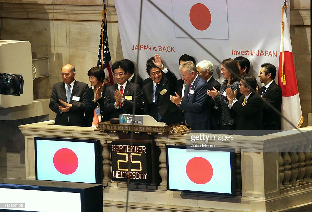 Japanese Prime Minister <a gi-track='captionPersonalityLinkClicked' href=/galleries/search?phrase=Shinzo+Abe&family=editorial&specificpeople=559017 ng-click='$event.stopPropagation()'>Shinzo Abe</a> (C) waves before ringing the closing bell at the New York Stock Exchange on September 25, 2013 in New York City. He gave a speech at the NYSE on 'Abenomics' and his country's economic recovery.