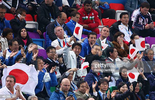 Japanese Prime Minister Shinzo Abe waves the national flag as he watches the Figure Skating Team Ladies Short Program with former Prime Minister and...