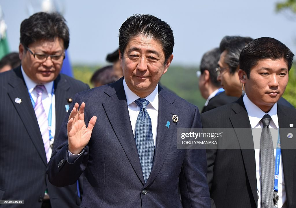 Japanese Prime Minister Shinzo Abe (C) waves to journalists as he leaves a press conference as the chairman, at the end of the two-day Group of Seven (G7) Summit meeting at Shima on May 27, 2016. Pumping up the world economy is an 'urgent priority' G7 leaders said on May 27, but left the door open for a go-your-own-way approach in a sign of lingering divisions over how to boost growth. / AFP / TORU