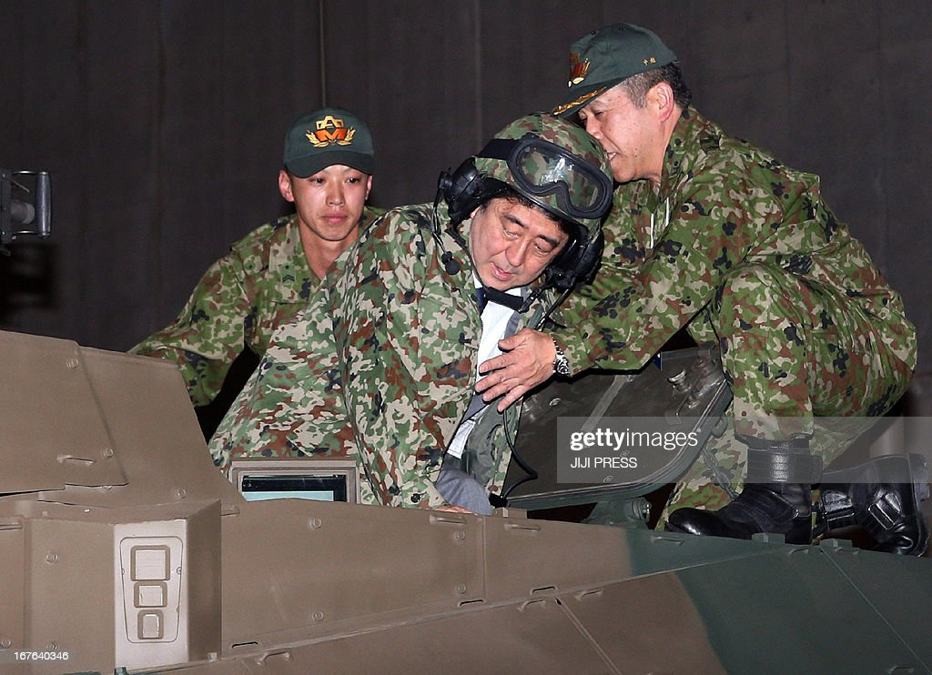 Japanese Prime Minister Shinzo Abe (C) wearing a camouflage jacket and helmet is helped by officers of Japanese Ground Defence Force as he enters a tank at an event, promoted by the Internet video sharing site in Chiba, suburban Tokyo on April 27, 2013. Abe visited the event as Japan will allow the use of Facebook, Twitter and other social networking websites in election campaigning for the upcoming Upper House election in July.