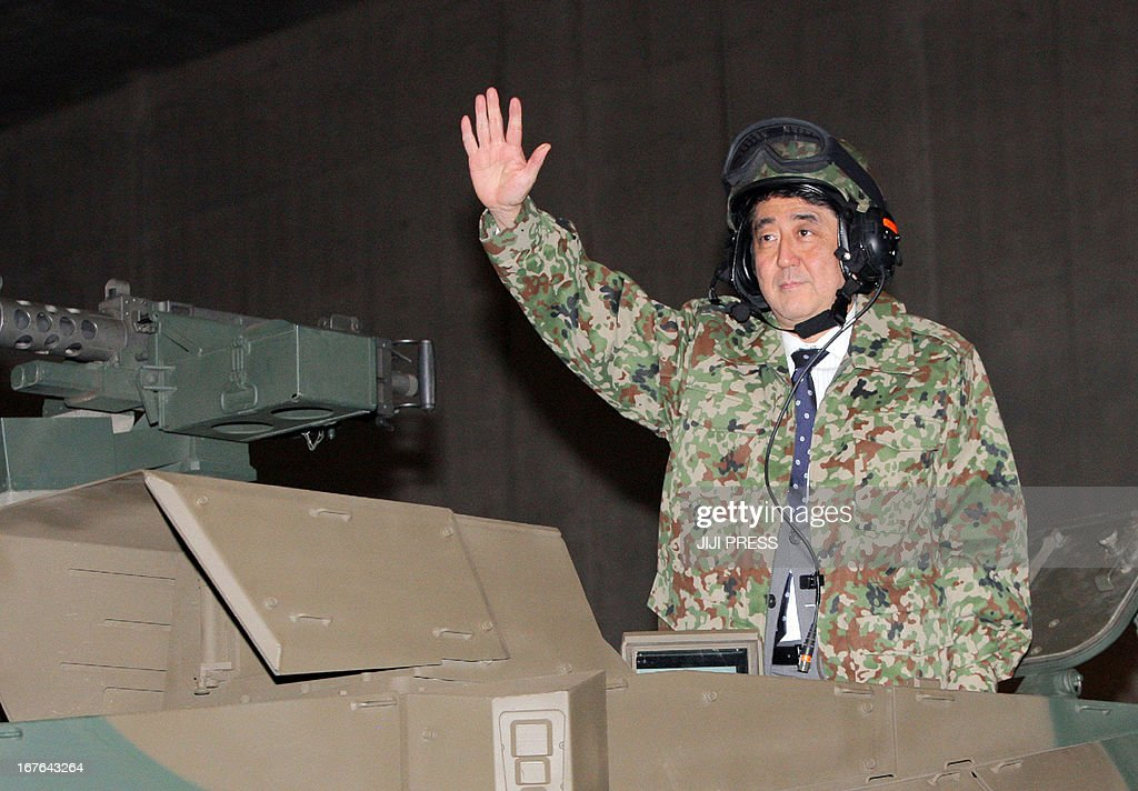 Japanese Prime Minister Shinzo Abe wearing a camouflage jacket and helmet waves from a tank of Japanese Ground Defence Force at an event, promoted by the Internet video sharing site in Chiba, suburban Tokyo on April 27, 2013. Abe visited the event as Japan will allow the use of Facebook, Twitter and other social networking websites in election campaigning for the upcoming Upper House election in July.