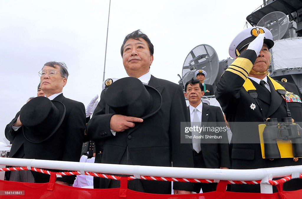 Japanese Prime Minister <a gi-track='captionPersonalityLinkClicked' href=/galleries/search?phrase=Yoshihiko+Noda&family=editorial&specificpeople=6441440 ng-click='$event.stopPropagation()'>Yoshihiko Noda</a> (C) and Defense Minister Satoshi Morimoto (L) attend the Japan Maritime Self-Defense Force Naval Fleet Review on October 14, 2012 at Sagami Bay, near Yokohama, Kanagawa, Japan.