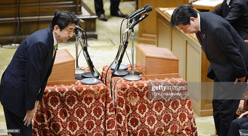 Japanese Prime Minister Yoshihiko Noda (R) bows to President of the main opposition Liberal Democratic Party (LDP) Shinzo Abe (L) before their one-on-one debate at the lower house on November 14, 2012. Noda said on November 14 he will dissolve parliament on November 16 to hold an election if his opponents play ball on reforming the electoral system. AFP PHOTO / Toru YAMANAKA