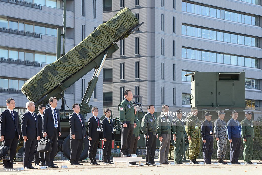 Japanese Prime Minister Yoshihiko Noda (C) gives a speech as he addresses soldiers while in front of a Patriot Advanced Capability-3 (PAC-3) missile launcher at the Defence Ministry in Tokyo on December 7, 2012. Japan on December 7 issued the order to shoot down a North Korean rocket if it threatens the nation's territory, the top government official said. Tokyo has readied surface-to-air missiles in and around Tokyo, as well as in Okinawa, and is putting its armed forces on standby ahead of Pyongyang's planned missile launch. AFP PHOTO / Toru YAMANAKA