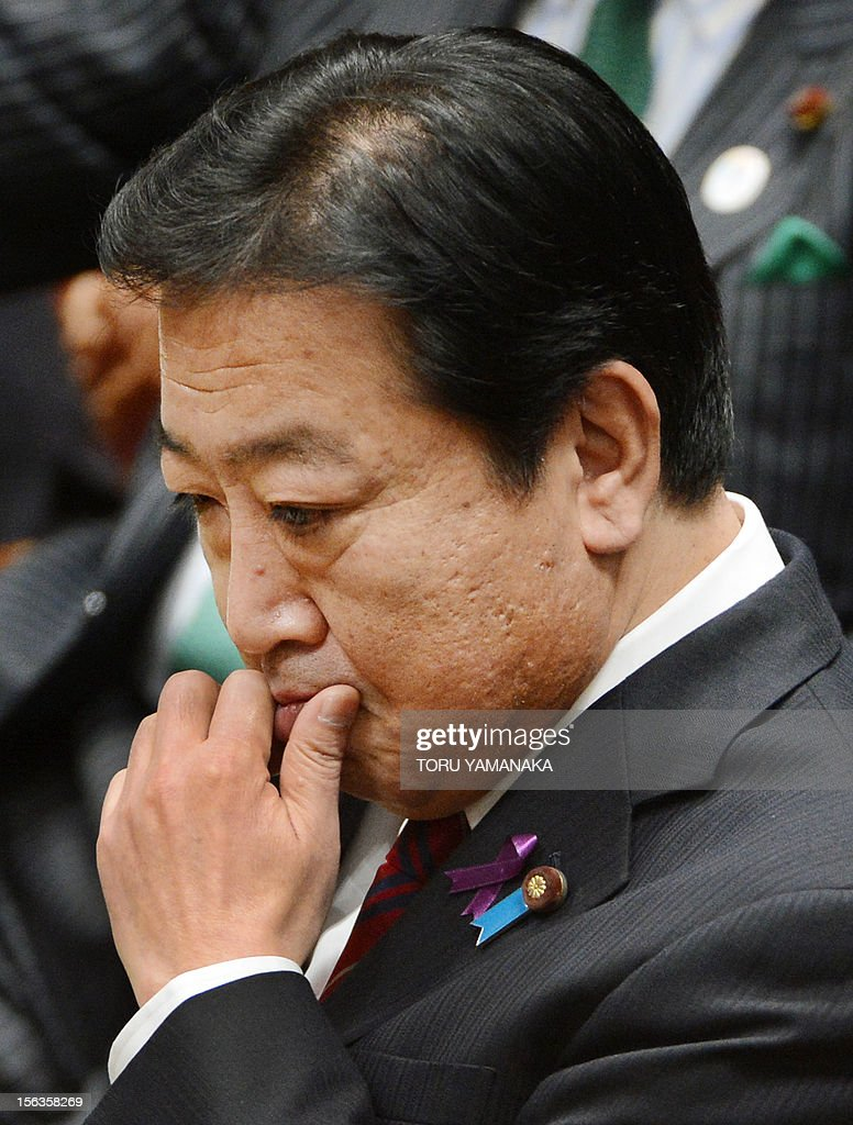 Japanese Prime Minister Yoshihiko Noda reacts as he listens to questions during a one-by-one debate with President of the main opposition Liberal Democratic Party (LDP) Shinzo Abe at the lower house on November 14, 2012. Noda said on November 14 he will dissolve parliament on November 16 to hold an election if his opponents play ball on reforming the electoral system. AFP PHOTO / Toru YAMANAKA