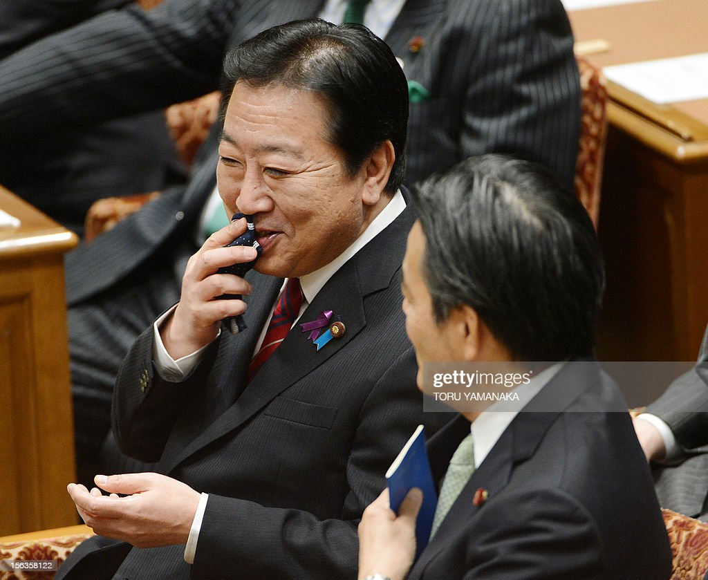 Japanese Prime Minister Yoshihiko Noda (L) shares a light moment with Deputy Prime Minister Katsuya Okada (R) before President of the main opposition Liberal Democratic Party (LDP) Shinzo Abe before their one-on-one debate at the lower house on November 14, 2012. Noda said on November 14 he will dissolve parliament on November 16 to hold an election if his opponents play ball on reforming the electoral system. AFP PHOTO / Toru YAMANAKA