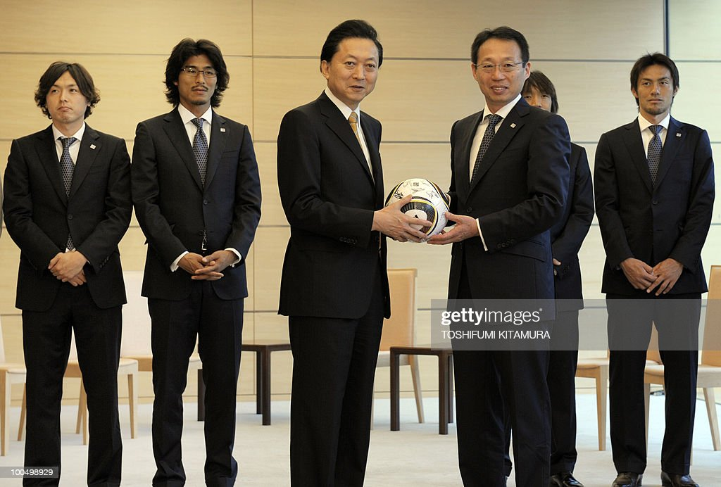 Japanese Prime Minister Yukio Hatoyama (3rd L) receives a signed ball from Japan National Football team head coach Takeshi Okada (3rd R) at Hatoyama's official residence in Tokyo on May 25, 2010 while players (L-R), Yasuhito Endo, Yuji Nakazawa, Shunsuke Nakamura and Seigo Narazaki stand in the background. The team will leave here on May 26 for a Switzerland training camp before joining the 2010 FIFA World Cup in South Africa.