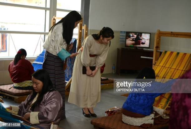 Japanese Princess Mako watches weavers of Bhutanese traditional costumes at the Royal Textile Academy in Thimphu during her visit to Bhutan on June 3...