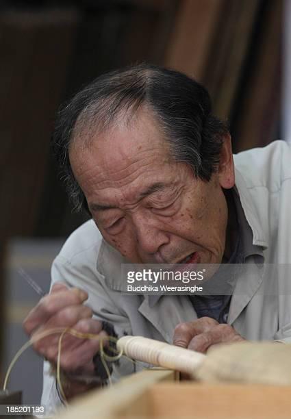 Japanese professional Tatami mat manufacturer Taizo Motoyama makes a Tatami at Motoyama Tatami Shop on October 18 2013 in Kyoto Japan Tatami mat is a...