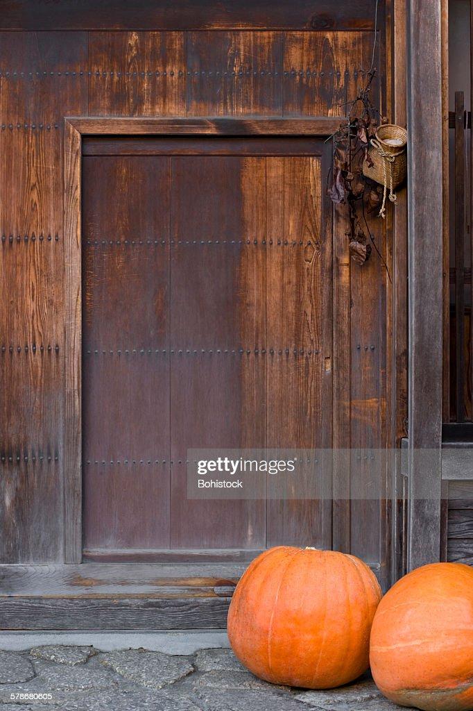 Japanese pumpkins by wooden doorway